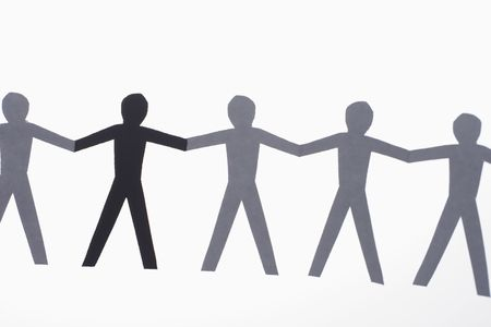 and the horizontal man: One black cutout paper person holding hands with group of white people. Stock Photo