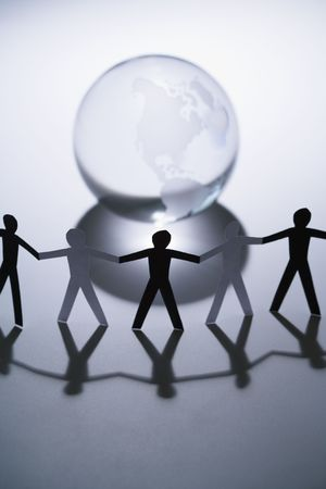 Black and white cutout paper people standing aroung Earth globe holding hands. Stock Photo - 2616812