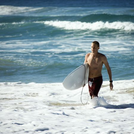 surfers: Young adult male walking ocean carrying surfboard in Surfers Paradise, Australia. Stock Photo