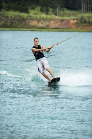 Caucasian young adult male wakeboarding on lake. photo