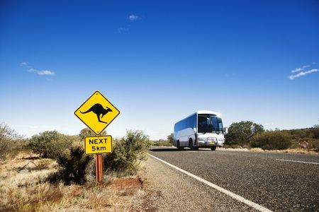 outback australia: Bus on two lane asphalt road in rural Australia with kangaroo crossing sign. Stock Photo