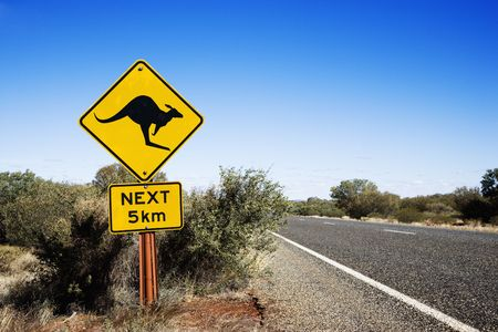 Kangaroo crossing sign by road in rural Australia.