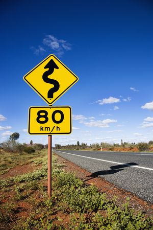 kilometer: Kilometer per hour speed limit and curve ahead road signs in rural Australia.