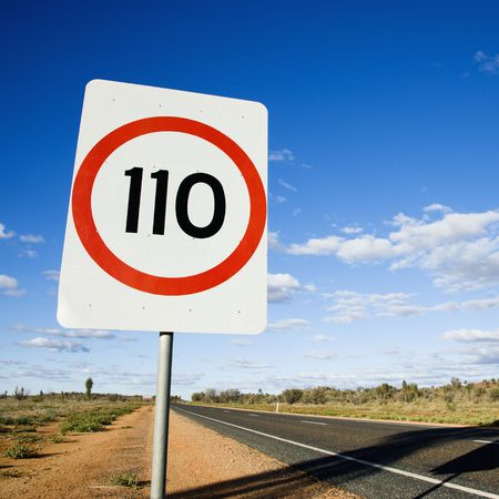 kilometer: Speed limit kilometer per hour road sign by road in rural Australia. Stock Photo