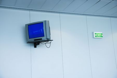 Monitor mounted to wall next to exit sign in airport photo