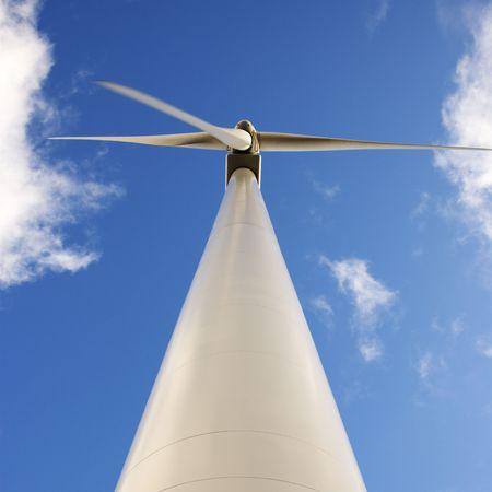 low perspective: Perspective shot of wind turbine against blue sky.