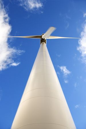 Perspective shot of wind turbine against blue sky. photo