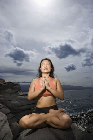 Asian woman sitting on rock by ocean in lotus pose with eyes closed in Maui, Hawaii photo