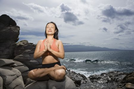 Asian woman sitting on rock by ocean in lotus pose with eyes closed in Maui, Hawaii Stock Photo - 2615954