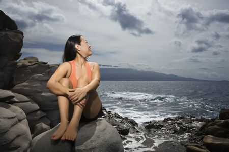 looking over: Asian woman sitting on rock by ocean looking over shoulder smiling in Maui, Hawaii