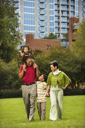 Family of four people walking in park smiling. photo