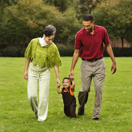 Mother and father helping toddler walk holding his hands in park. Stock Photo - 2622899