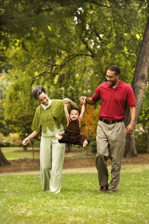 Mother and father swinging toddler holding his hands in park. Stock Photo - 2616073