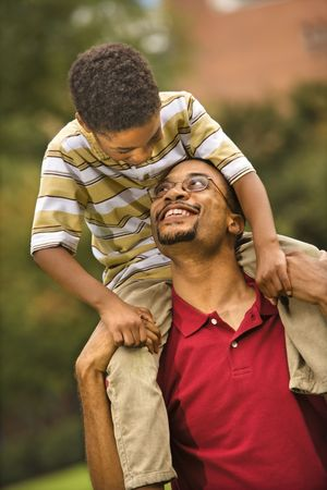 Father carrying his son on his shoulders smiling and looking at eachother. Stock Photo - 2615955