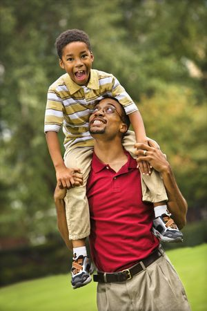 Father carrying his son on his shoulders smiling and looking at eachother. Stock Photo - 2616019