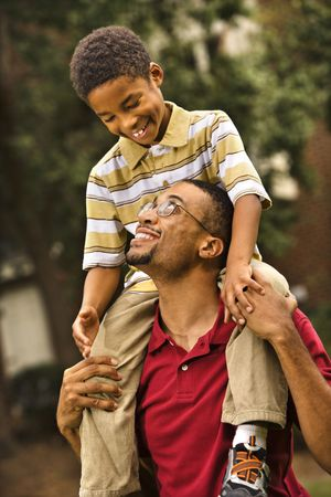 Father carrying his son on his shoulders smiling and looking at eachother. photo