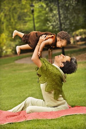 Woman holding toddler up in air and smiling in park. Stock Photo - 2622903
