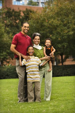 Family of four standing in park smiing. Stock Photo - 2616071