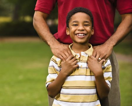 Father standing behind son with hands on his shoulders as boy smiles. photo