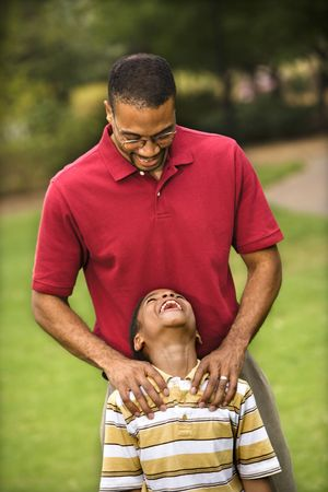 Father standing behind son with hands on his shoulders as boy smiles. Stock Photo - 2615960