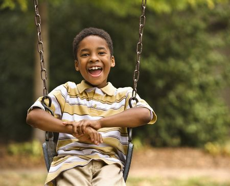 Happy smiling boy on swing in park playground. photo