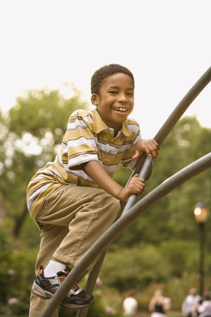 Boy climbing metal bars on playground in park smiling. photo