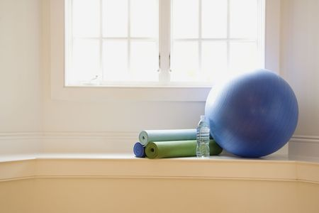 balance ball: Balance ball, exercise mats and bottled water at gym by window.