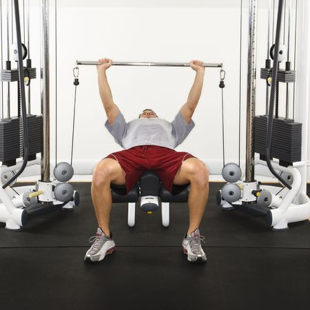 Man at gym lifting weights on weight machine. Stock Photo - 2615891