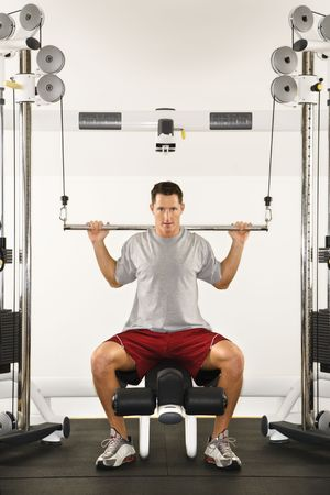 weight machine: Man at gym lifting weights on weight machine.