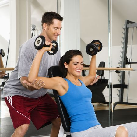 Man assisting woman at gym with hand weights smiling. Stock Photo