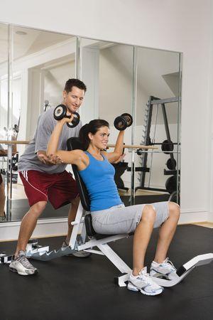 levantando pesas: Hombre ayudar a la mujer en el gimnasio con pesas mano sonriente.