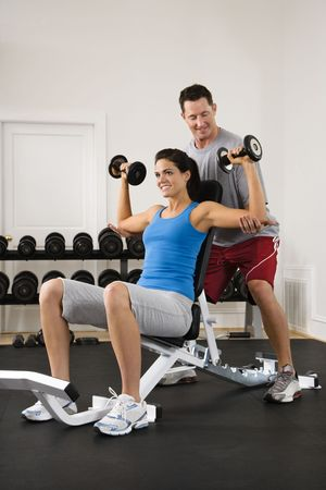 Man assisting woman at gym with hand weights smiling. Stock Photo - 2622855