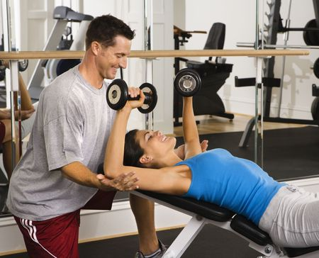 Man assisting woman at gym with hand weights smiling. Stock Photo - 2622897
