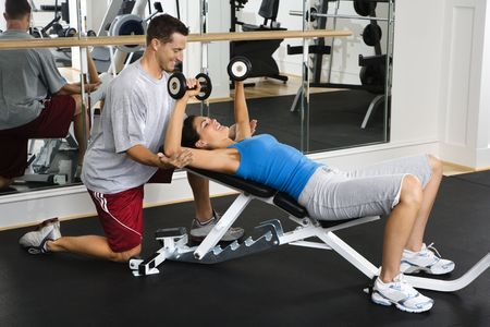Man assisting woman at gym with hand weights smiling. photo
