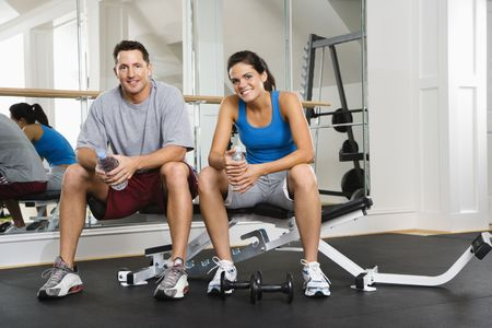 Man and woman sitting on exercise machine talking holding water bottles. photo