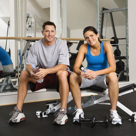 Man and woman sitting on exercise machine smiling holding water bottles. photo