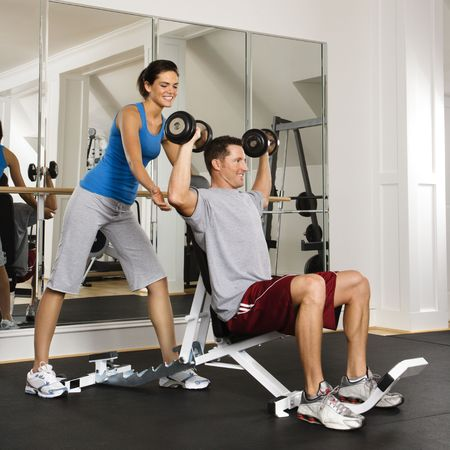Woman spotting man lifting weights at gym. Stock Photo - 2615912