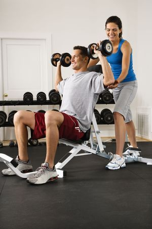Woman assisting man lifting weights at gym. photo