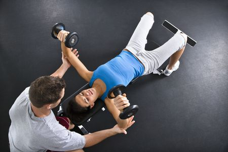 free weight: Man assisting woman lifting weights at gym. Stock Photo