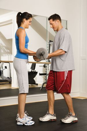 Man and woman lifting weights in gym. Stock Photo - 2615880