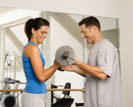 Man and woman lifting weights in gym. Stock Photo - 2622862