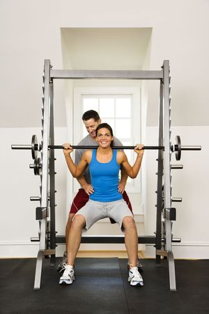 assisted: Woman lifting weights in gym being assisted by man.