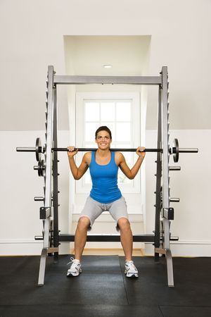 Woman lifting weights in gym smiling. Stock Photo - 2615657