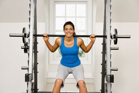 trapezius: Woman lifting weights in gym smiling.