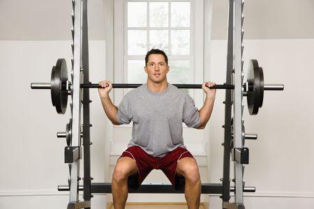 trapezius: Pesos de elevaci�n del hombre en gym.