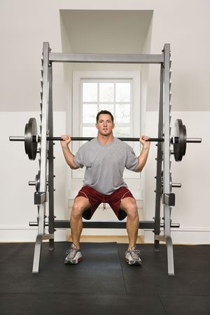 lifting: Man lifting weights in gym.