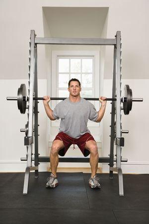 levantando pesas: Pesos de elevaci�n del hombre en gym.