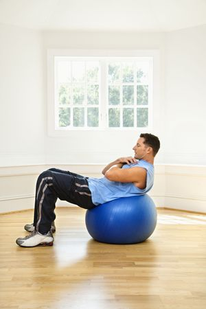 sit ups: Man doing sit ups on balance ball. Stock Photo