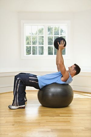 balance ball: Man lifting medicine ball while on balance ball. Stock Photo