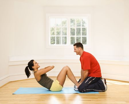 situp: Man holding womans feet down as she does sit up exercises.